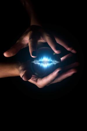 Handen die kristallen bol met geluidsgolf