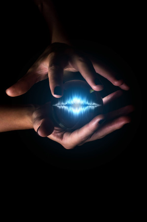 Hands holding crystal ball containing sound wave