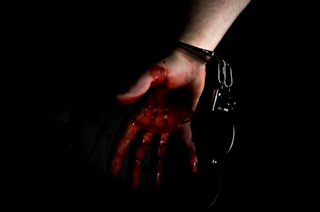 Bloody murderers hand in handcuffs in dark moody lighting