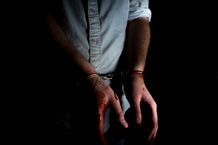 red handed: Bloody male hands handcuffed in dark moody lighting