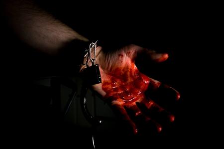 red handed: Bloody murderers hand in handcuffs in dark moody lighting