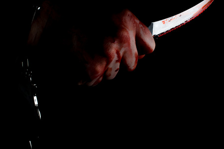 Murderer bloody hand holding knife in moody dark lighting Stock Photo