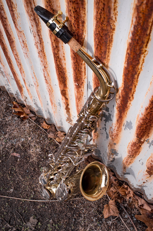 Jazz musical instrument saxophone with rusty fence background Stock Photo