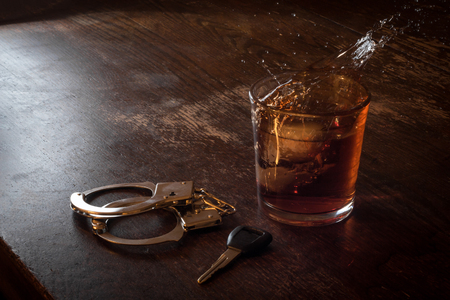 Rocks glass of whisky with handcuffs and keys symbolizing drunk driving arrest Stock Photo