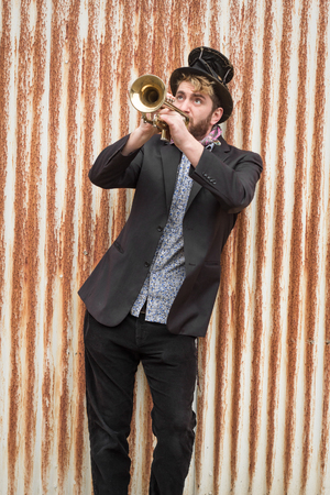 Stylish bearded gypsy plays trumpet by rusty fence