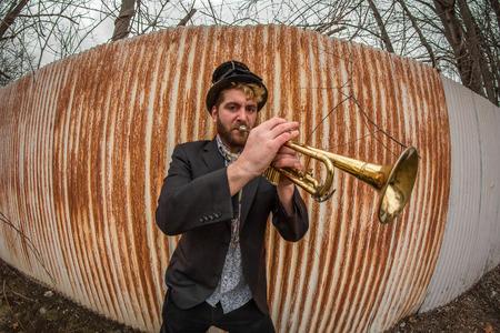gitana: gitano con barba estilo toca la trompeta por la valla oxidada