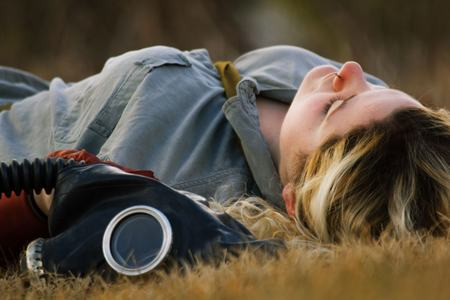 Pretty girl resting in field with authentic Russian gas mask