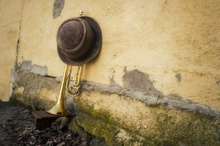 pealing: Old worn trumpet against grungy wall with pork pie style top hat