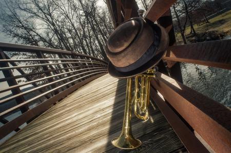 lost lake: Old worn trumpet with pork pie hat on bridge