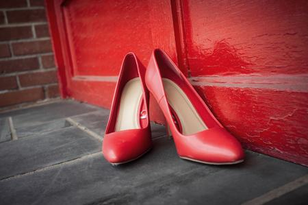 Red high heel shoes on street outdoors with nobody wearing them