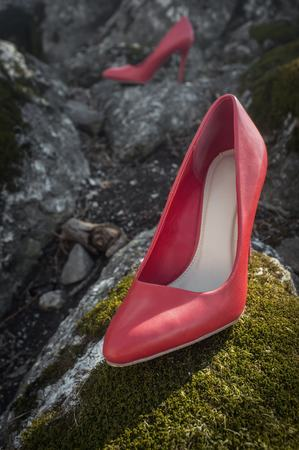 Red high heel shoes on mossy rocks with nobody wearing them