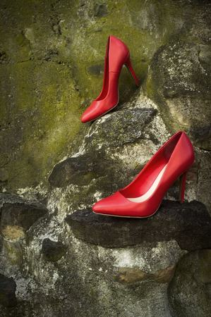 Red high heel shoes mossy green rocks with nobody wearing them