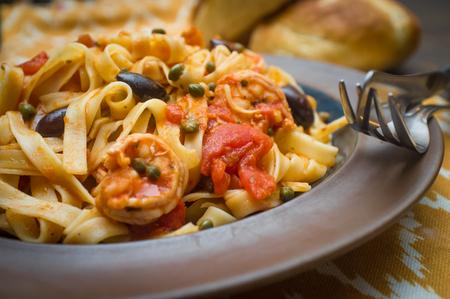 Delicious Spaghetti alla puttanesca with jumbo shrimp and fresh italian bread