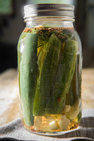 marinated gherkins: Homemade rustic organic pickled cucumbers on wooden table Stock Photo