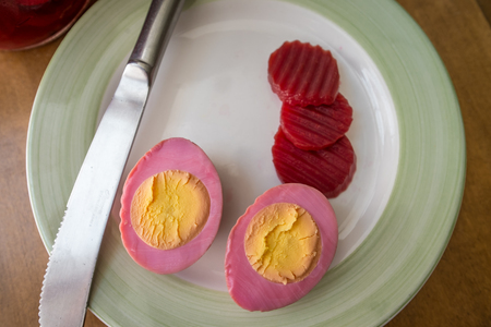 Sliced organic pickled beet eggs on wooden table Stock Photo
