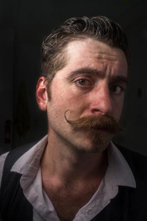 Caucasian hipster man with large handlebar mustache wearing a dress shirt and suit vest Foto de archivo