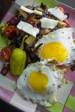 Eggs sunnyside up with pepperoncini and home fries Stock Photo