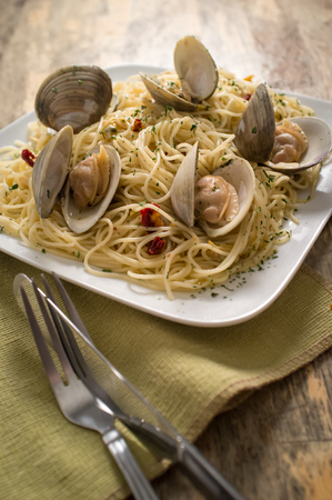 Spaghetti with fresh cooked baby clam sauce on rustic wood table Stock Photo