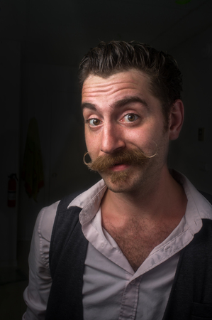 Caucasian hipster man with large handlebar mustache wearing a dress shirt and suit vest Stock Photo