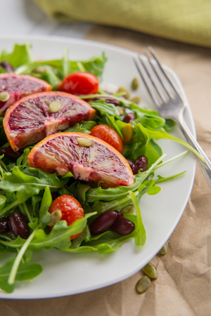 Healthy arugula and tomato salad with red blood orange slices Stock Photo