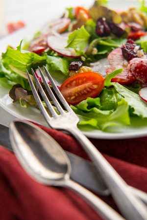 Fresh organic romaine lettuce salad with walnuts radishes and strawberries Stock Photo