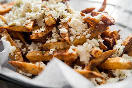 Delicious Mediterranean street cart fried potatoes with feta cheese herbs and spices