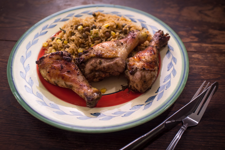 Jamaican jerk chicken legs with corn and bean rice
