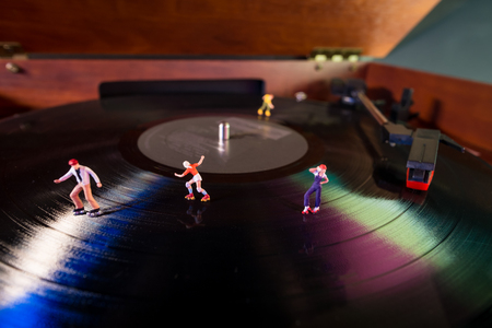 Miniature roller skating figures on vintage vinyl record in macro closeup