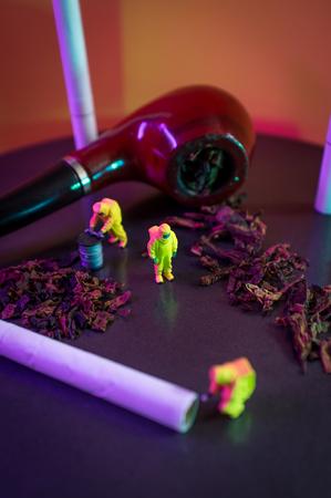 Miniature hazmat team inspects hazardous tobacco products Stock Photo