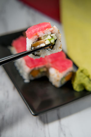 Japanese tuna salmon and cucumber sushi roll with wasabi and pickled ginger
