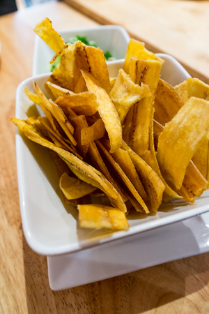 Crispy fried plantain chips with fresh spicy guacamole