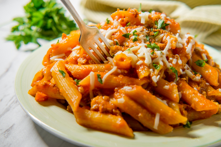 Penne Italian ragu alla Bolognese sauce with shredded mozzarella and toasted garlic bread crumbs Stock Photo