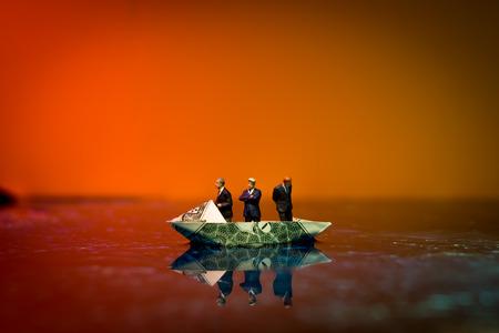 Miniature figurine businessmen ride on dollar bill origami yacht Imagens
