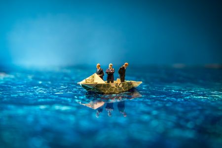 Miniature figurine businessmen ride on dollar bill origami yacht Stock Photo