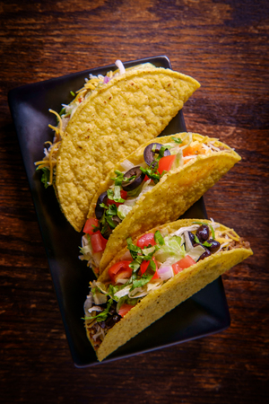 Mexican beef tacos loaded with toppings including olives shredded lettuce and tomatoes Stock Photo