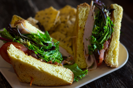 Turkey BLT sandwich on texas toast with sesame seed chips and hummus