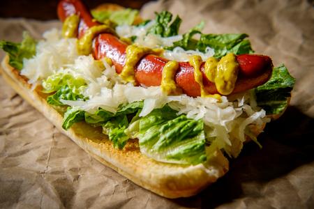 Fancy grilled hotdog with sauerkraut lettuce and spicy mustard