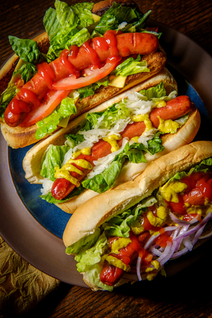 Fancy grilled hotdogs with many toppings including relish and sauerkraut