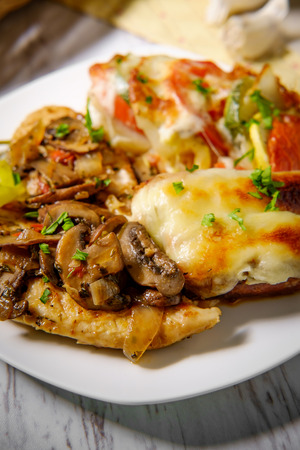 Italian chicken marsala with French vegetable tian and stuffed sausage Stock Photo