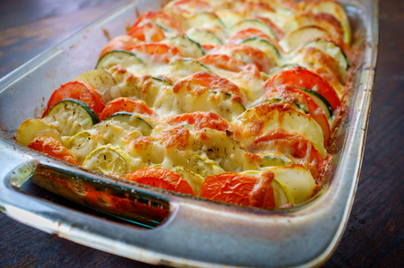 Rustic French vegetable tian casserole with dark moody lighting