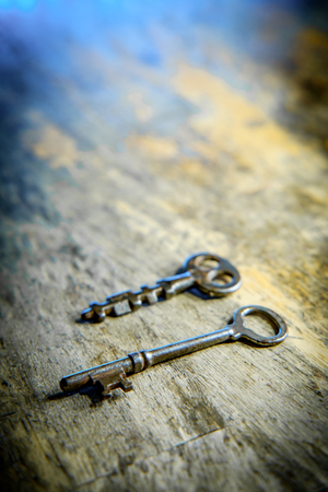 Old antique skeleton key on distressed textured wooden background Stock Photo