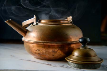 Fluitende hete theepot op aanrecht met stoom uit gekookt water
