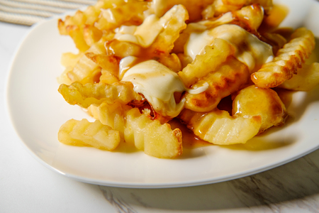 Canadian Poutine crinkle-cut fries with gravy and cheese curd Foto de archivo