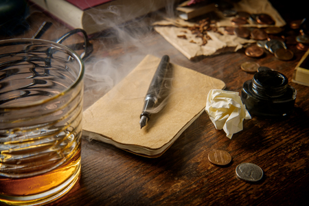 Writer's desk with pen and ink whisky pipe and glasses