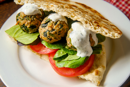 Mediterranean turkey meatball sandwich on pita bread with dill yogurt sauce