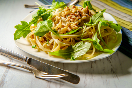 Vegetarian fettuccine with walnuts and arugula in a sweet white wine garlic sauce Stok Fotoğraf
