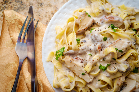 Authentic Italian fettuccine alfredo pasta dish with grilled chicken breast