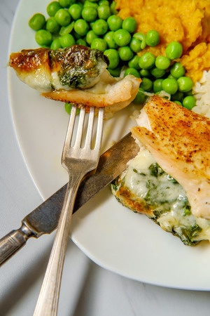 Italian grilled chicken breast stuffed with provolone cheese and spinach with peas mashed sweet potatoes and rice