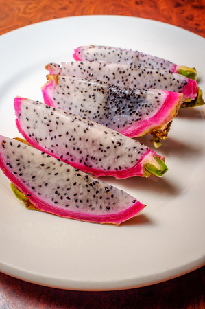 Juicy exotic sliced pink and white dragonfruit on plate Stock Photo