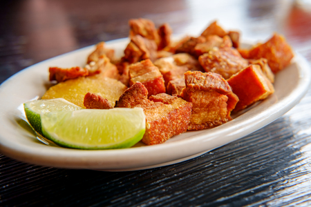 Colombian fried pork belly, chicharrón colombiano, with sliced limes